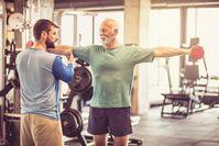 Imagen sobre el tema del entrenador personal y el hombre mayor haciendo ejercicio con pesas