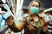 Imagen sobre el tema de la mujer de pie con máscara en el supermercado