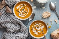 Imagen sobre el tema de dos tazones de sopa de calabaza en una mesa de otoño