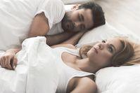 Imagen sobre el tema de la dama insomne junto al hombre dormido en la cama