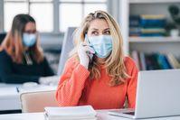 Imagen sobre el tema de la mujer sentada con máscara en la oficina