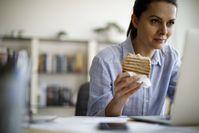 Imagen sobre el tema de una mujer sentada frente a la computadora y comiendo
