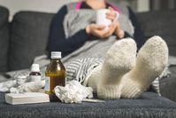 Imagen sobre el tema de la mujer en el sofá con medicina para el resfriado