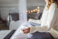 Imagen sobre el tema de la mujer en suéter de lana meditando o haciendo yoga con las piernas cruzadas