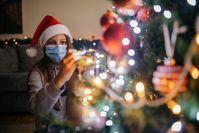 Imagen sobre el tema de la mujer con máscara decora el árbol de Navidad