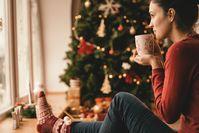 Imagen sobre el tema de la mujer bebiendo té junto al árbol de Navidad