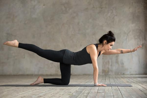 Mujer en posición cuadrúpeda mientras estira las piernas