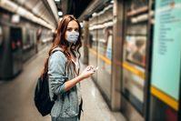 Imagen sobre el tema de la mujer de pie con máscara en la estación de tren