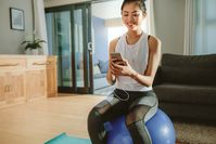 Imagen sobre el tema de la mujer con smartphone en fitness ball