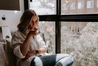 Imagen sobre el tema de la mujer sentada junto a la ventana y bebiendo té