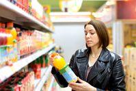 Mujer mirando una botella en el supermercado