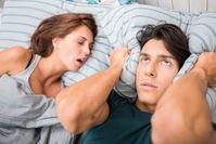 Imagen sobre el tema Mujer joven ronca junto a su pareja en la cama, quien está molesta y presiona la almohada sobre sus orejas