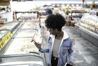 Imagen sobre el tema de la mujer joven mirando la lista de ingredientes de un producto en el supermercado