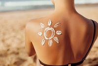 Imagen sobre el tema de la mujer sentada en la playa con protector solar en el hombro