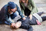 Imagen sobre el tema de los transeúntes cuidar a la persona que yace inmóvil en el suelo