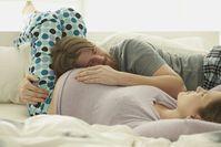 Imagen sobre el tema de la pareja abrazándose en el sofá embarazo