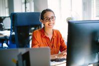 Imagen sobre el tema Mujer joven sentada en la oficina frente a la PC