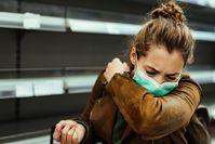 Imagen sobre el tema de una mujer con máscara que estornuda en el hueco de su brazo.