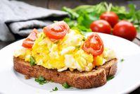 Imagen sobre el tema de los huevos revueltos en una rebanada de pan adornado con cuartos de tomate