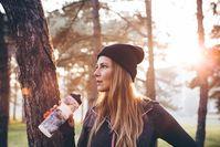 Imagen sobre el tema del corredor con sombrero en el bosque bebe de la botella de agua