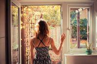 Imagen sobre el tema de una mujer de pie frente a una puerta de patio abierta