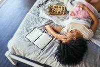 Imagen sobre el tema de la mujer acostada en la cama con dolor de estómago y una bolsa de agua caliente